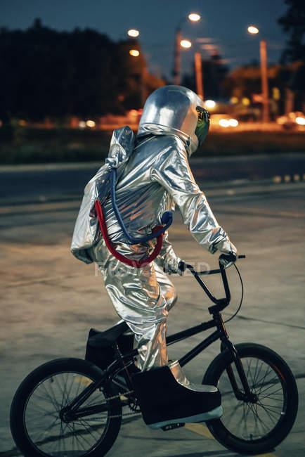 Космонавтом в місті вночі на стоянці їзди BMX Bike — стокове фото