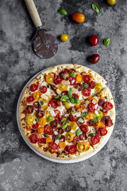 Нарізаний піци з помідорами та базиліком листя — стокове фото