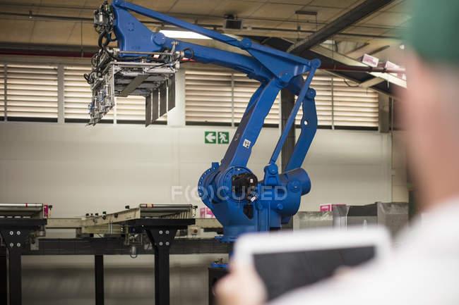 Trabajador que usa la tableta en fábrica - foto de stock