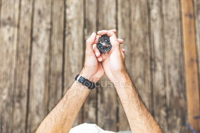 Close-up of man on boardwalk holding a compass — Stock Photo