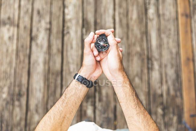 Primer plano del hombre en el paseo marítimo sosteniendo una brújula - foto de stock