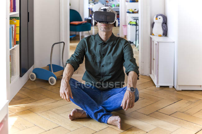Mature man sitting on the floor at home using Virtual Reality Glasses — Stock Photo