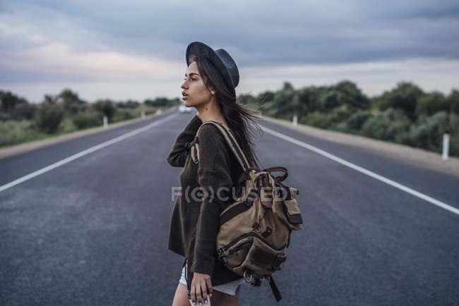Portrait of hitchhiking young woman with backpack and beverage standing on lane — Stock Photo