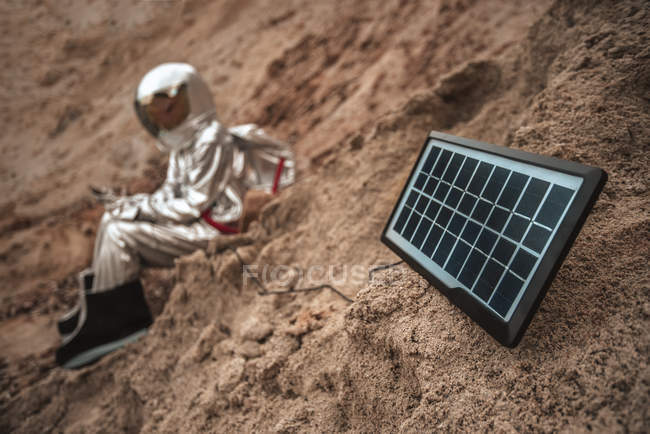 Spaceman sitting on nameless planet, charging device with solar panel — Stock Photo