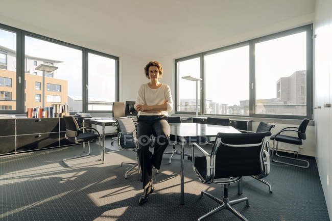Successful businesswoman sitting on desk in her office with arms crossed — Stock Photo