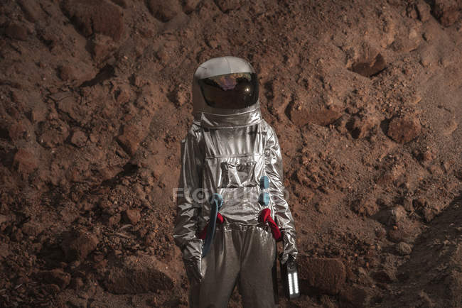 Spaceman exploring nameless planet, holding torch — Stock Photo