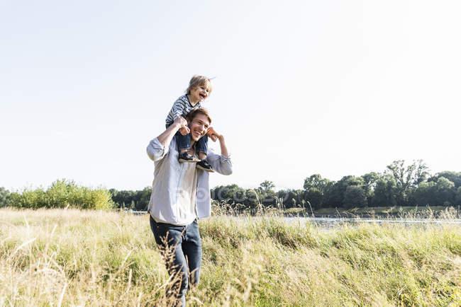 Père et fils s'amusent à la rivière le jour ensoleillé de l'été — Photo de stock