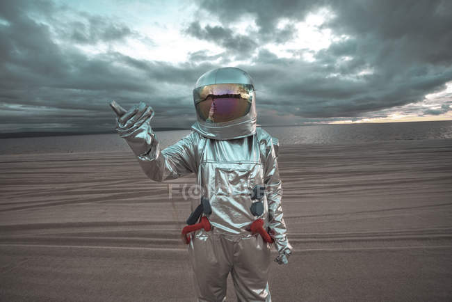 Spaceman pointing at something on nameless planet — Stock Photo