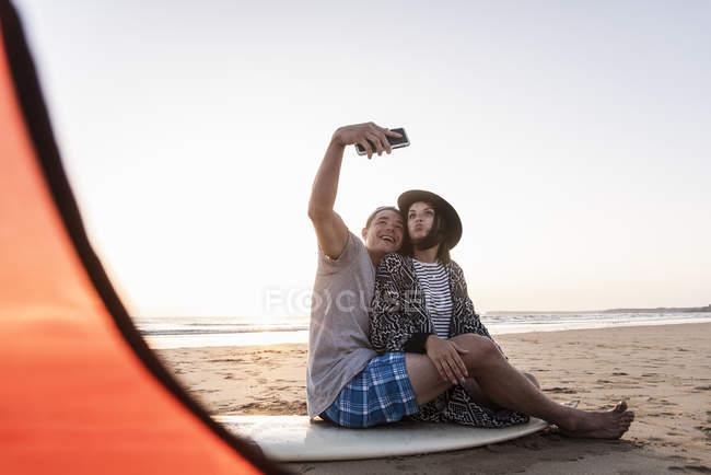 Coppia campeggio in spiaggia, prendendo selfie con smartphone — Foto stock