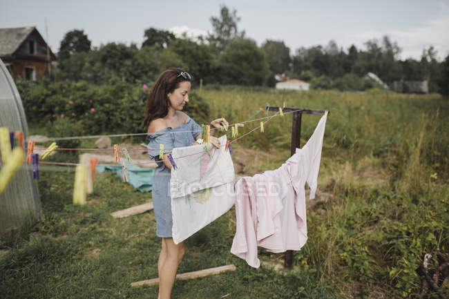 Жінка кладе білизну в саду. — стокове фото