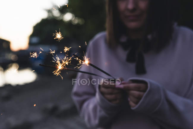 Young woman holding sparklers in the evening — Stock Photo