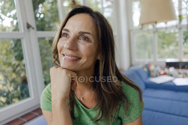 Sonriente mujer madura en el sofá en casa soñando - foto de stock