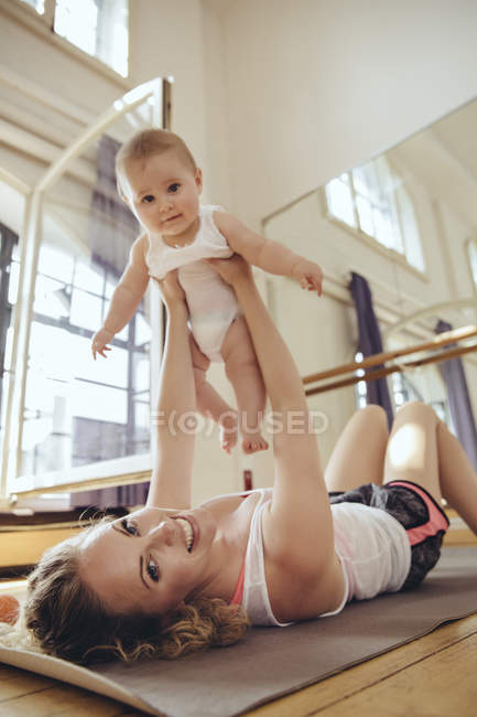 Mother working out on yoga mat while holding up her baby — Stock Photo