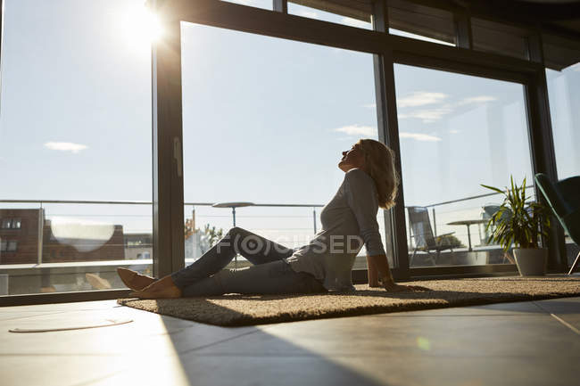 Relaxed mature woman sitting on carpet in sunlight at home — Stock Photo