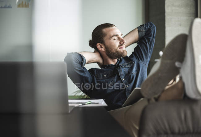 Relaxed smiling businessman sitting in office with closed eyes — стокове фото