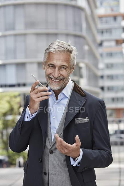 Портрет смеющегося взрослого бизнесмена разговаривающего по мобильному телефону — стоковое фото