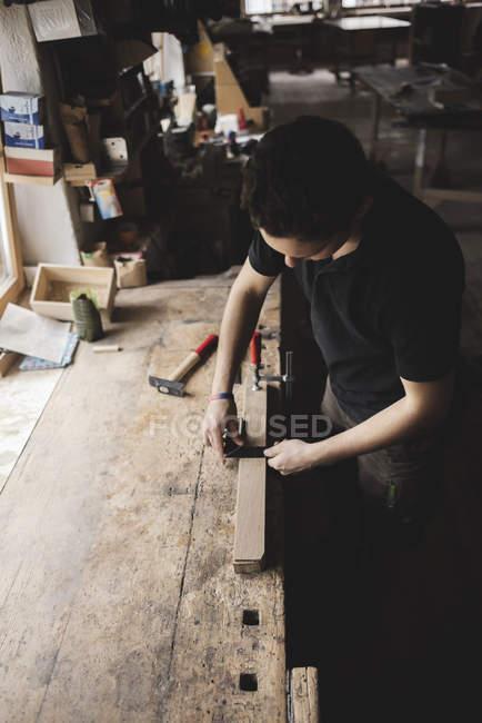 Tischler misst Stück Holz in Werkstatt — Stockfoto