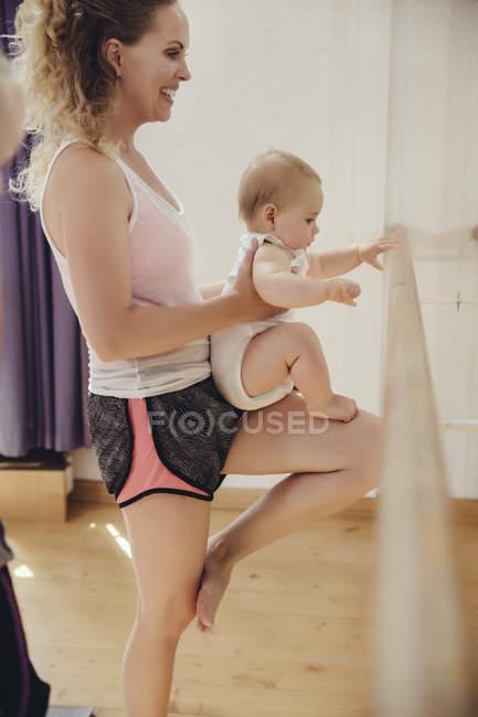 Due madri che reggono i loro bambini piccoli alla sbarra in studio di danza — Foto stock