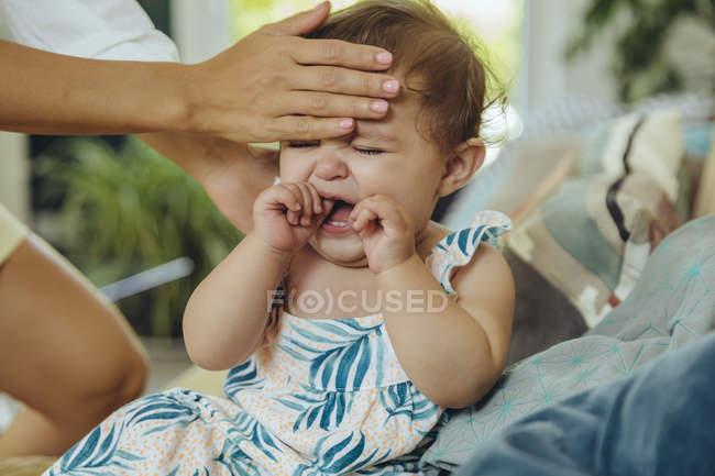 Madre che prende la temperatura della sua bambina piangente — Foto stock