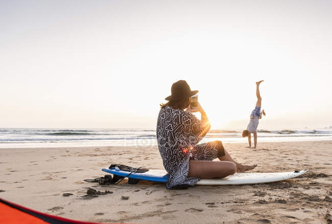Young woman sitting on surfboard, taking photo of young man, practicing handstands on beach — Stock Photo