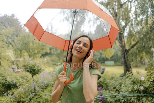 Счастливая зрелая женщина, стоящая под дождём под зонтиком и слушающая музыку в наушниках — стоковое фото