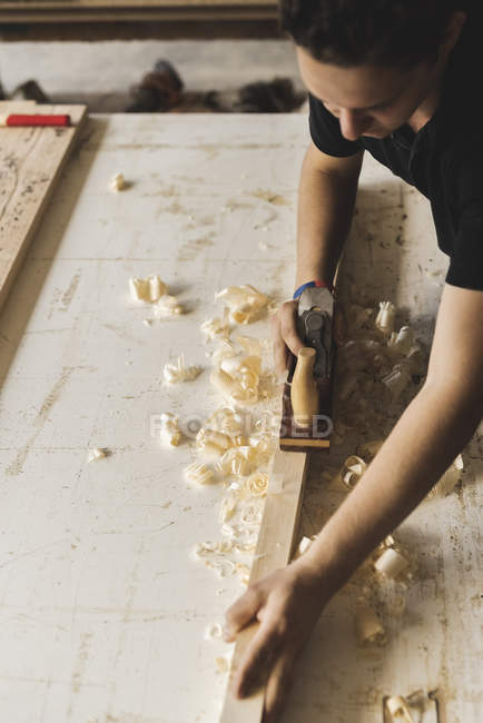 Плотник с помощью плоскости на куске дерева в мастерской — стоковое фото
