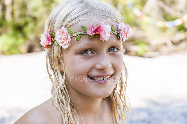 Portrait of smiling girl wearing flower crown outdoors in summer — Stock Photo