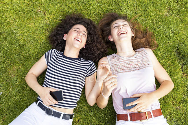 Two happy female friends lying down on grass and having fun — Stock Photo