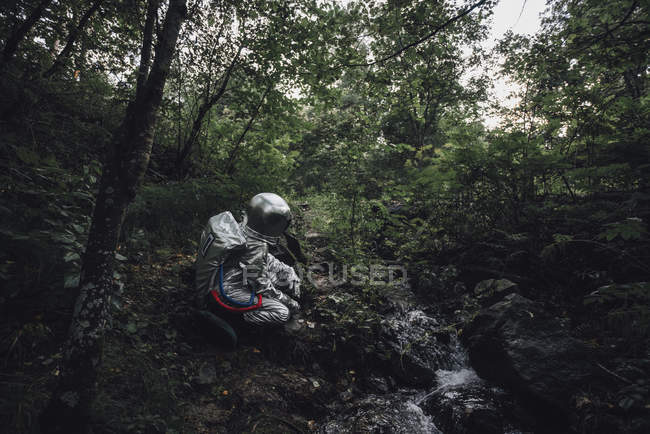 Spaceman exploring nature, crouching at brook in forest — Foto stock