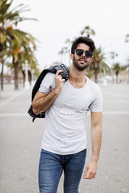 Retrato de jovem legal no calçadão com palmas — Fotografia de Stock