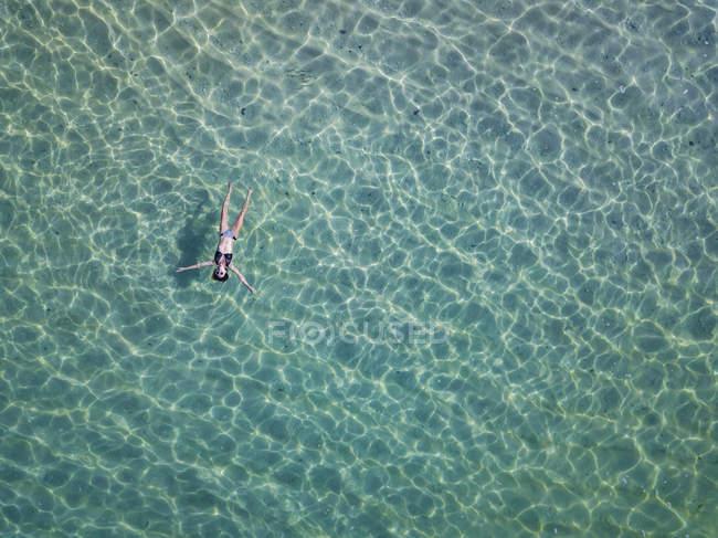 Indonesia, Bali, Melasti, Aerial view of Karma Kandara beach, woman floating on water — Stock Photo