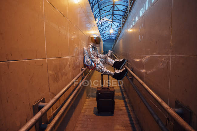 Spaceman in city at night with rolling suitcase in narrow passageway — Stock Photo