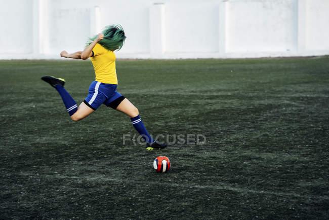 Junge Frau spielt Fußball auf Fußballplatz Schießen Ball — Stockfoto
