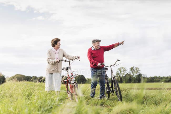 Coppia senior con biciclette passeggiando nel paesaggio rurale — Foto stock