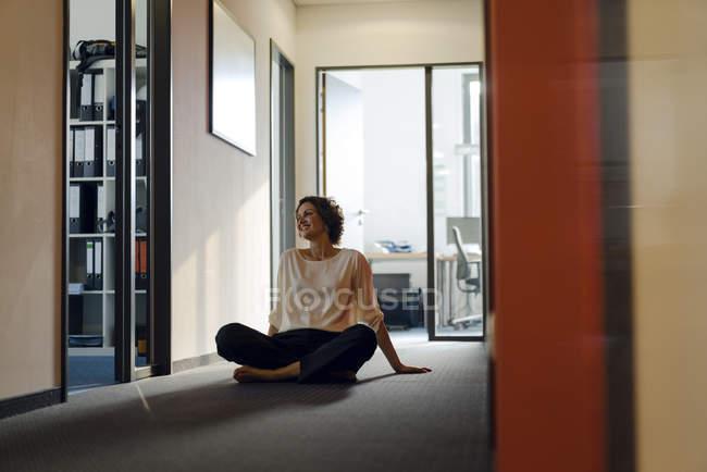 Geschäftsfrau sitzt querbeinig im Büro — Stockfoto