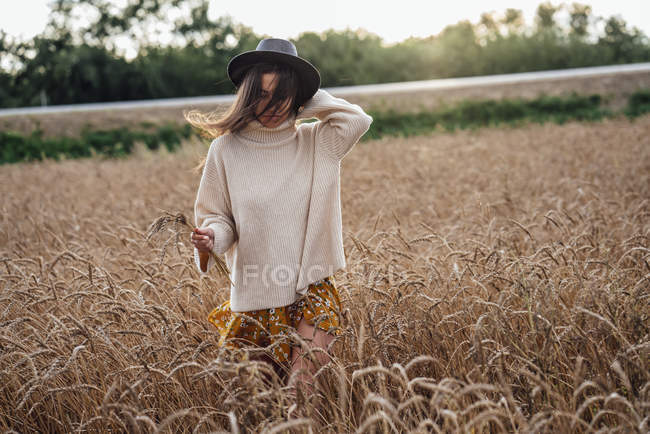 Young woman wearing hat and oversized turtleneck pullover walking in corn field — Photo de stock