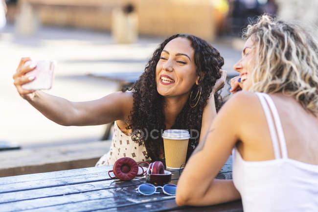 Счастливые подруги, делающие селфи за столом — стоковое фото