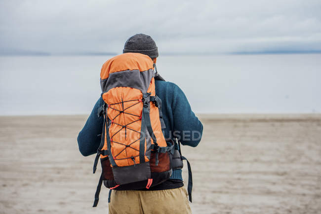 Back view of Man with big orange backpack at lake — Stock Photo