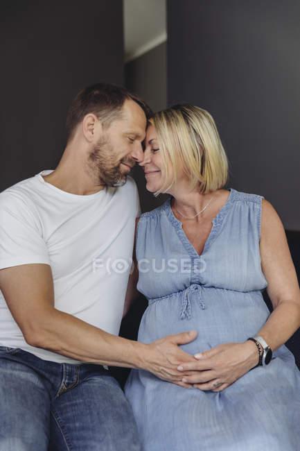 Hombre maduro y esposa embarazada sentada en la cama y tocando el vientre - foto de stock