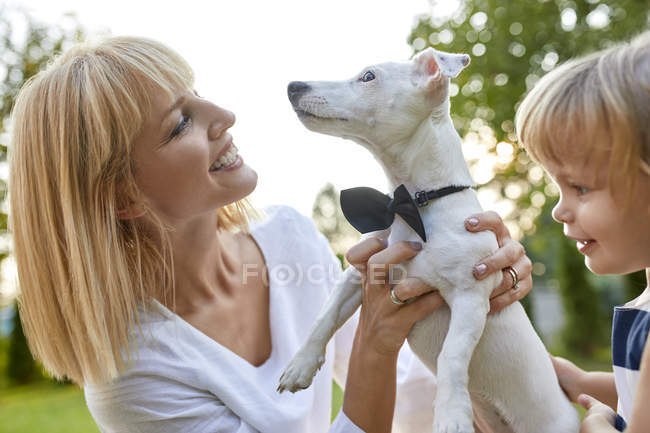 Happy woman with daughter holding dog wearing a bowtie outdoors — Stock Photo