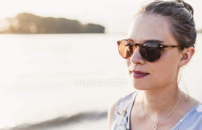 Young thoughtful woman wearing sunglasses at riverbank — Stock Photo