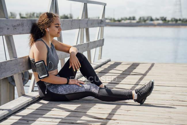 Молодая атлетка в наушниках отдыхает на берегу реки — стоковое фото