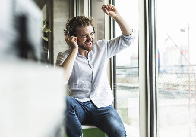 Jeune homme occasionnel enthousiaste écoutant la musique avec des écouteurs à la fenêtre — Photo de stock