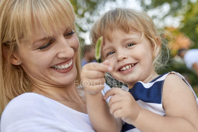 Happy mother with her daughter holding a stalk outdoors — Stock Photo