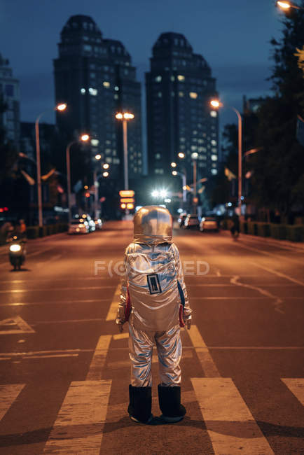 Rear view of spaceman standing on street in city at night — Stock Photo
