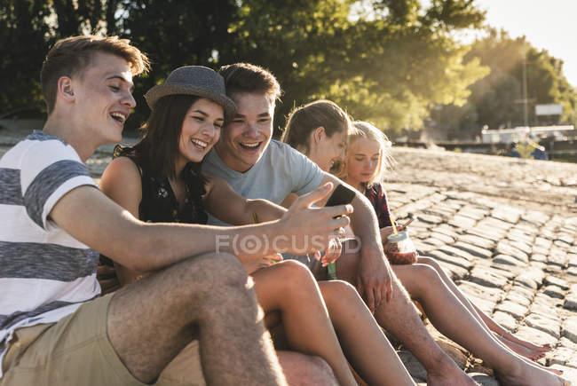 Gruppe von Freunden sitzt mit erfrischenden Getränken und Mobiltelefonen auf Kopfsteinpflaster — Stockfoto