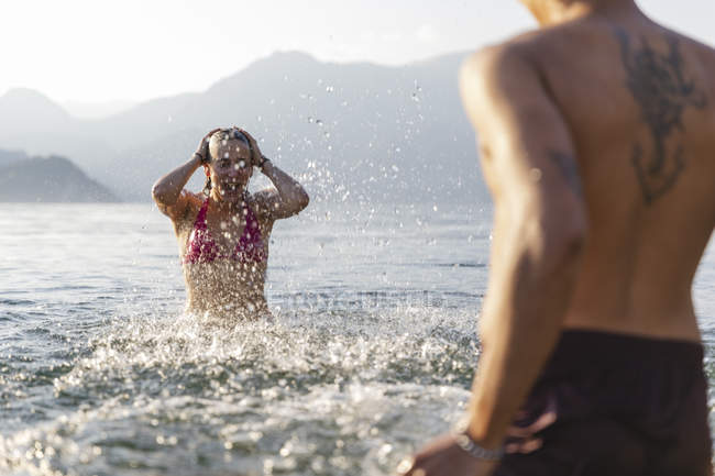 Felice giovane coppia che gioca in un lago — Foto stock