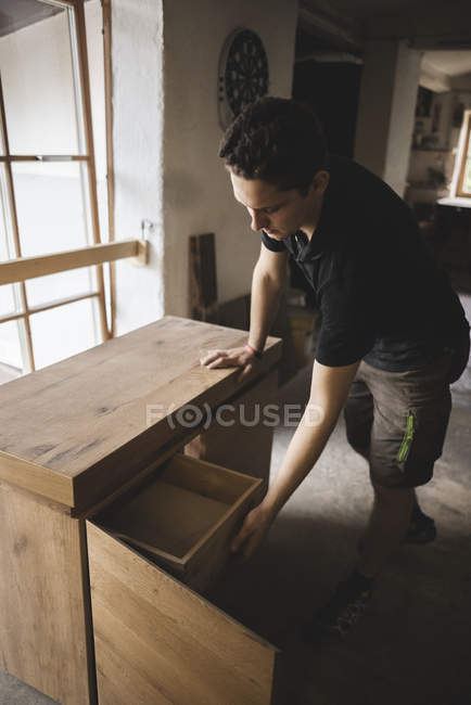 Carpenter in workshop testing chest of drawers — Stock Photo