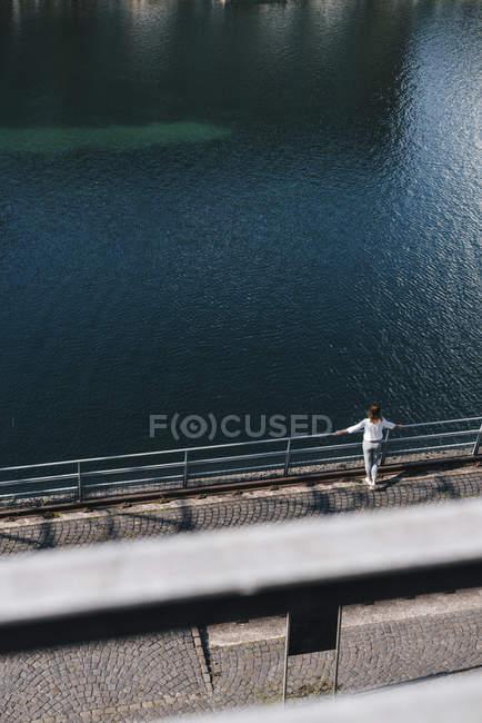 Женщина, стоящая у реки и смотрящая на вид — стоковое фото