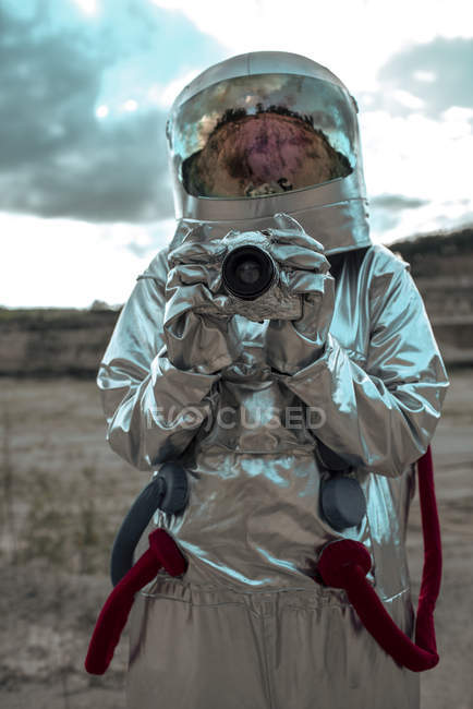 Spaceman on nameless planet taking picture with camera — Stock Photo